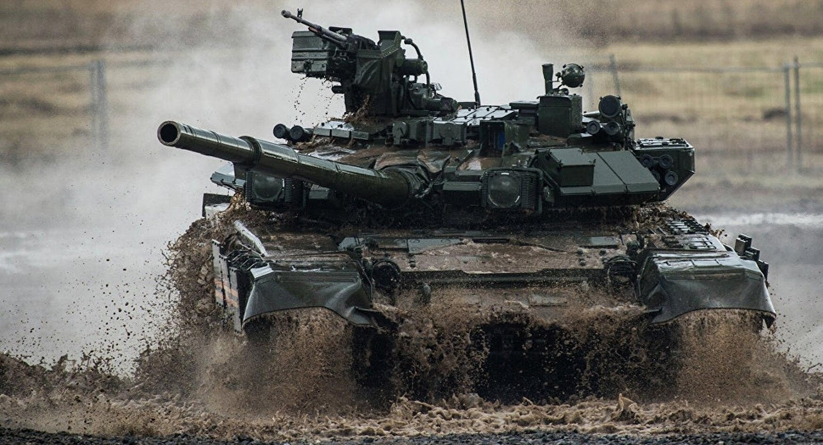 A Russian T-90 main battle tank variant cruises through mud and water during a demonstration. (Ramil Sitdikov/Sputnik)