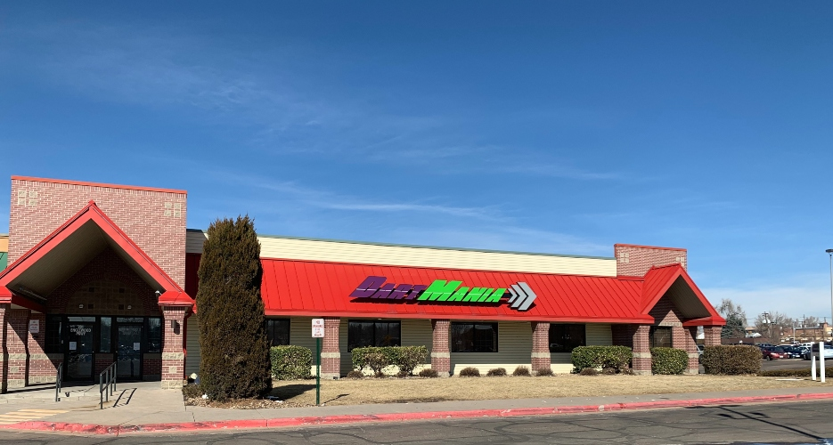 Photo of retail space available for sublease at 301 Englewood Parkway in Englewood, Colorado. Shows front of building with a sign saying DartMania in purple & green letters.