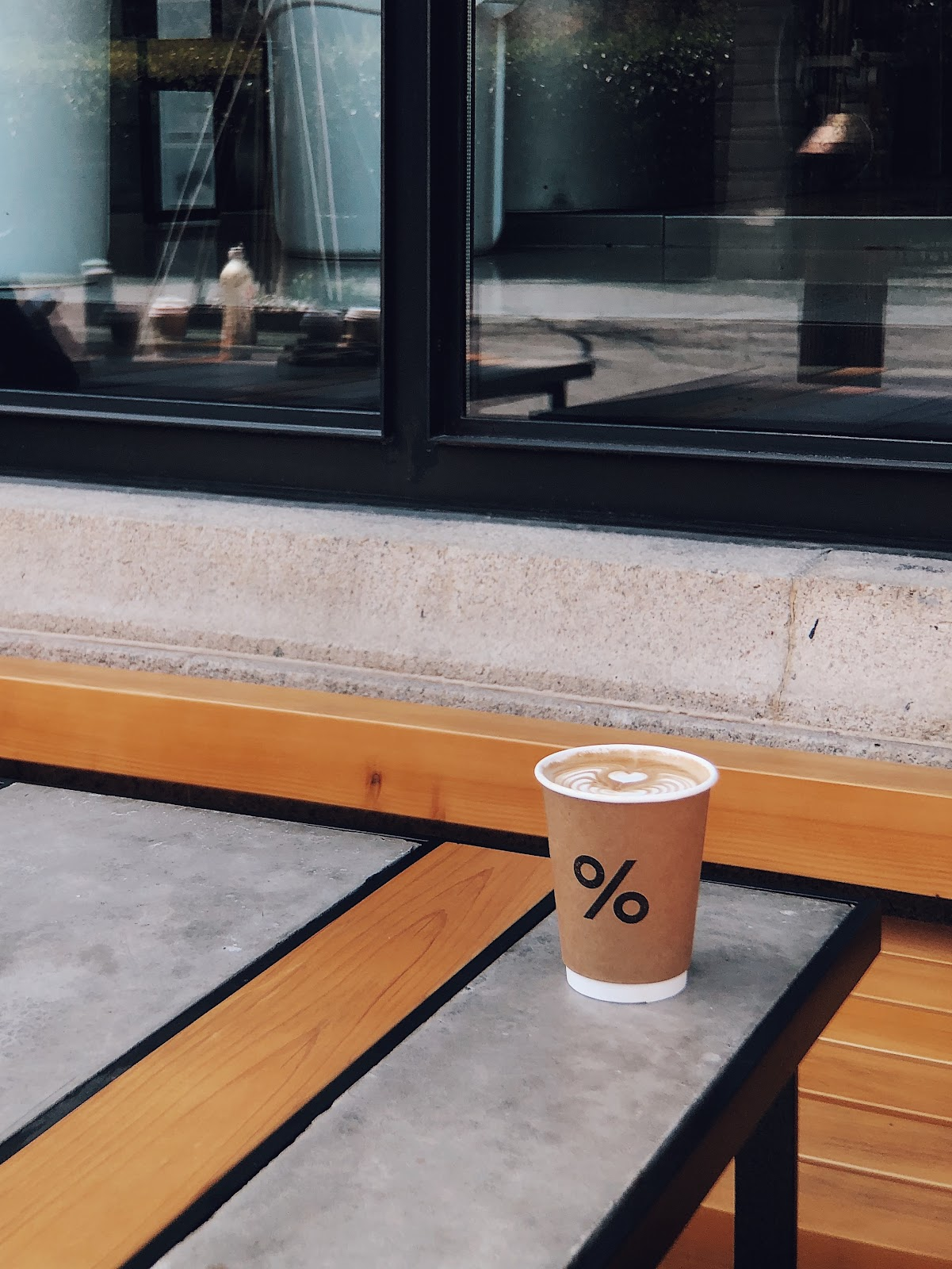 A latte in a paper cup at a coffee shop outside the window on a table. Reduce waste by bringing your own cup.