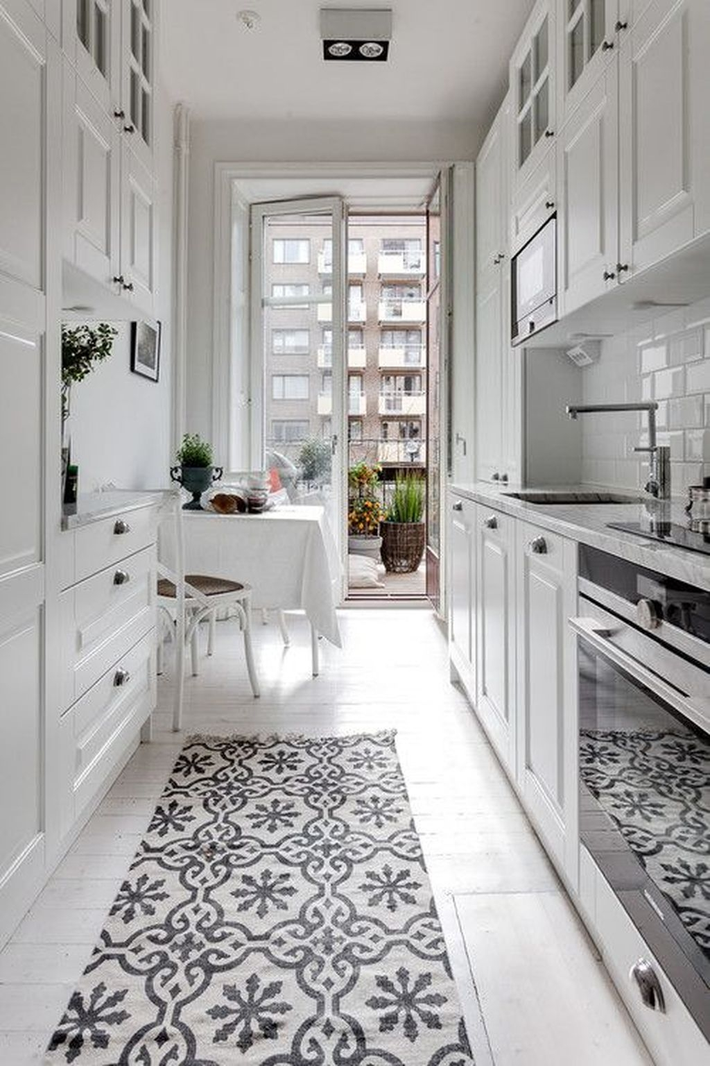 small galley kitchen in an apartment with bright white finishes, with personality added by a patterned black and white runner rug