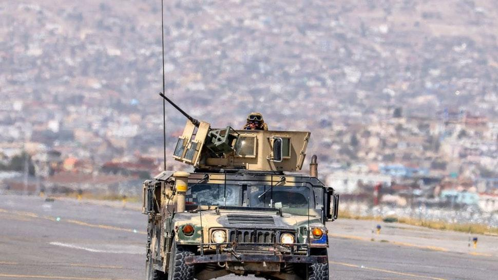 Taliban fighters patrol in an armored vehicle at the airport in Kabul on September 13, 2021. (Photo by Karim SAHIB / AFP) (Photo by KARIM SAHIB/AFP via Getty Images)