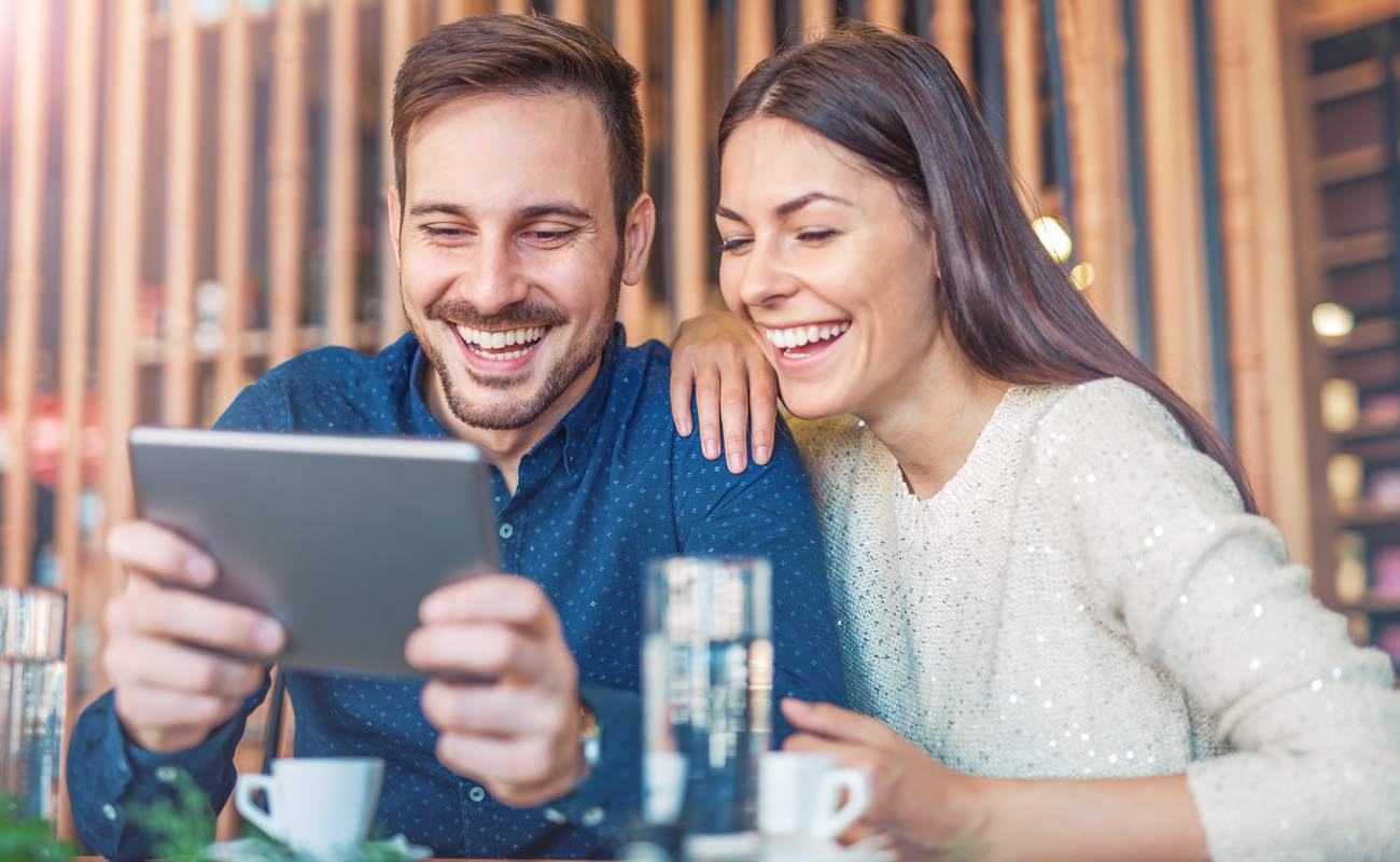 couple sitting in a cafe, drinking coffee and having fun with a tablet device