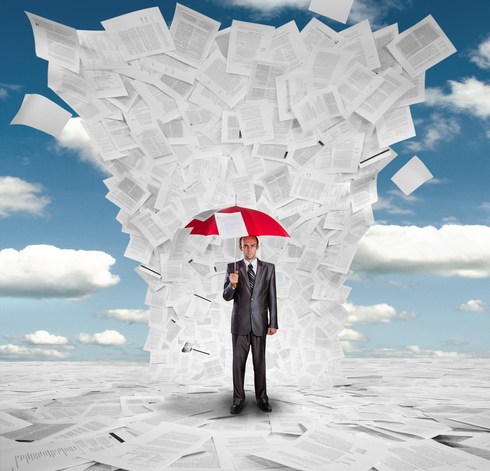 Man holding an umbrella under an avalanche of applicant forms