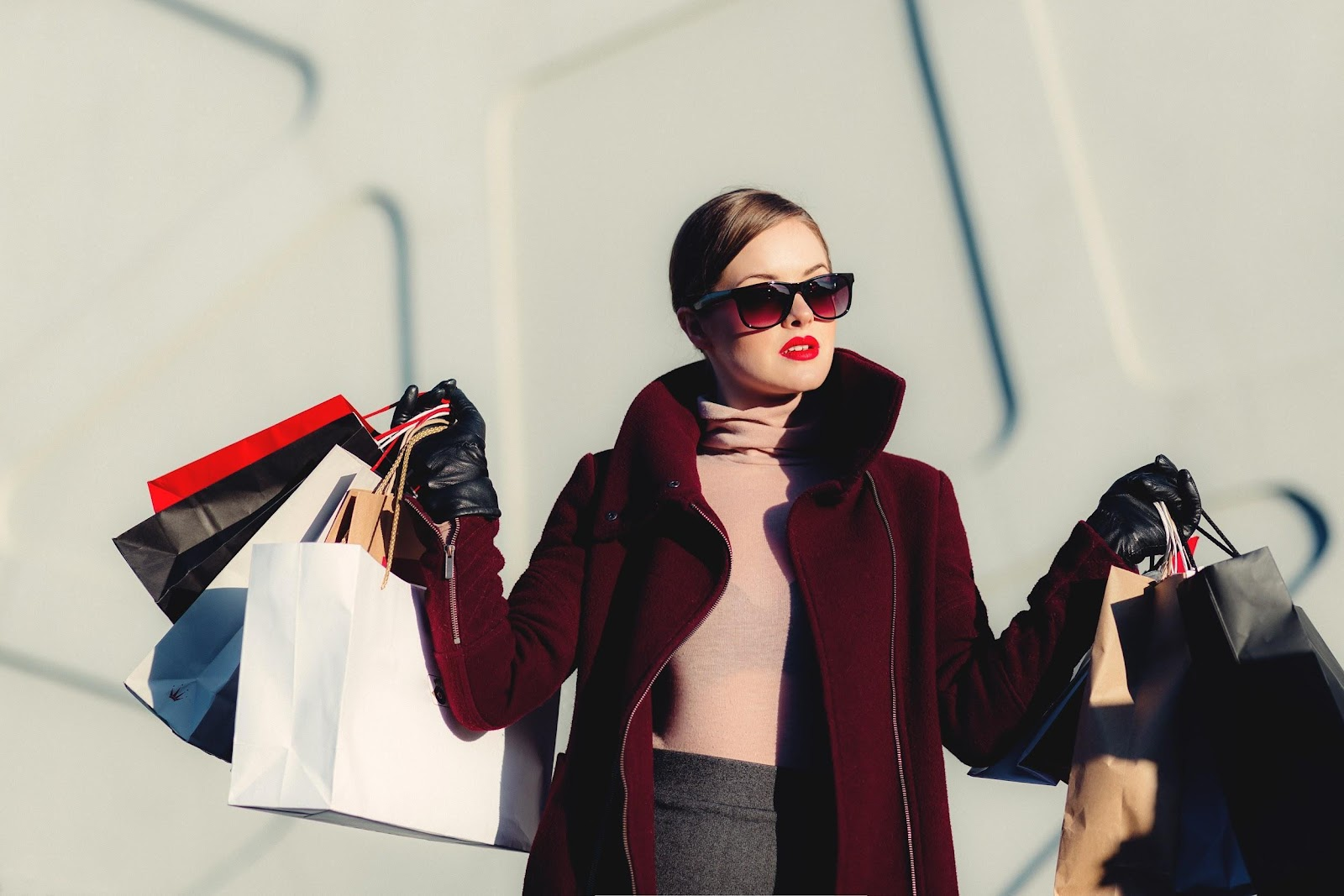Woman carrying bags of fashion designer clothing.