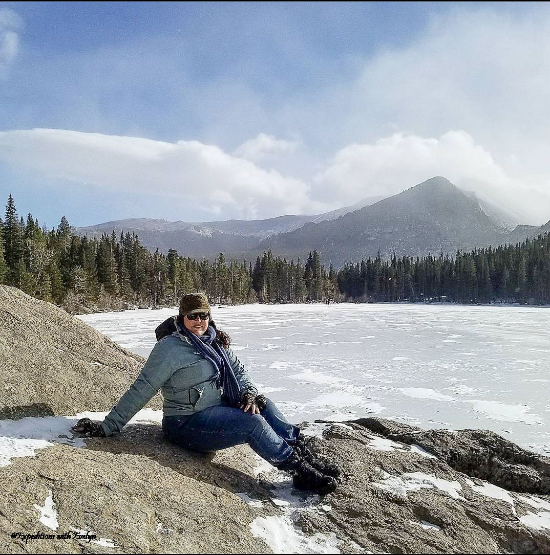 A female hiker in a coat, snowboots, and hat sits on a rock by a frozen lake surrounded by pine trees.  A tall mountain peak dominates the background. National Park Reservations 2021 are needed to visit Bear Lake in Rocky Mountain National Park.