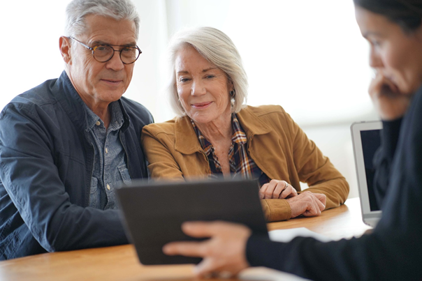 woman showing her tablet to an old man and woman