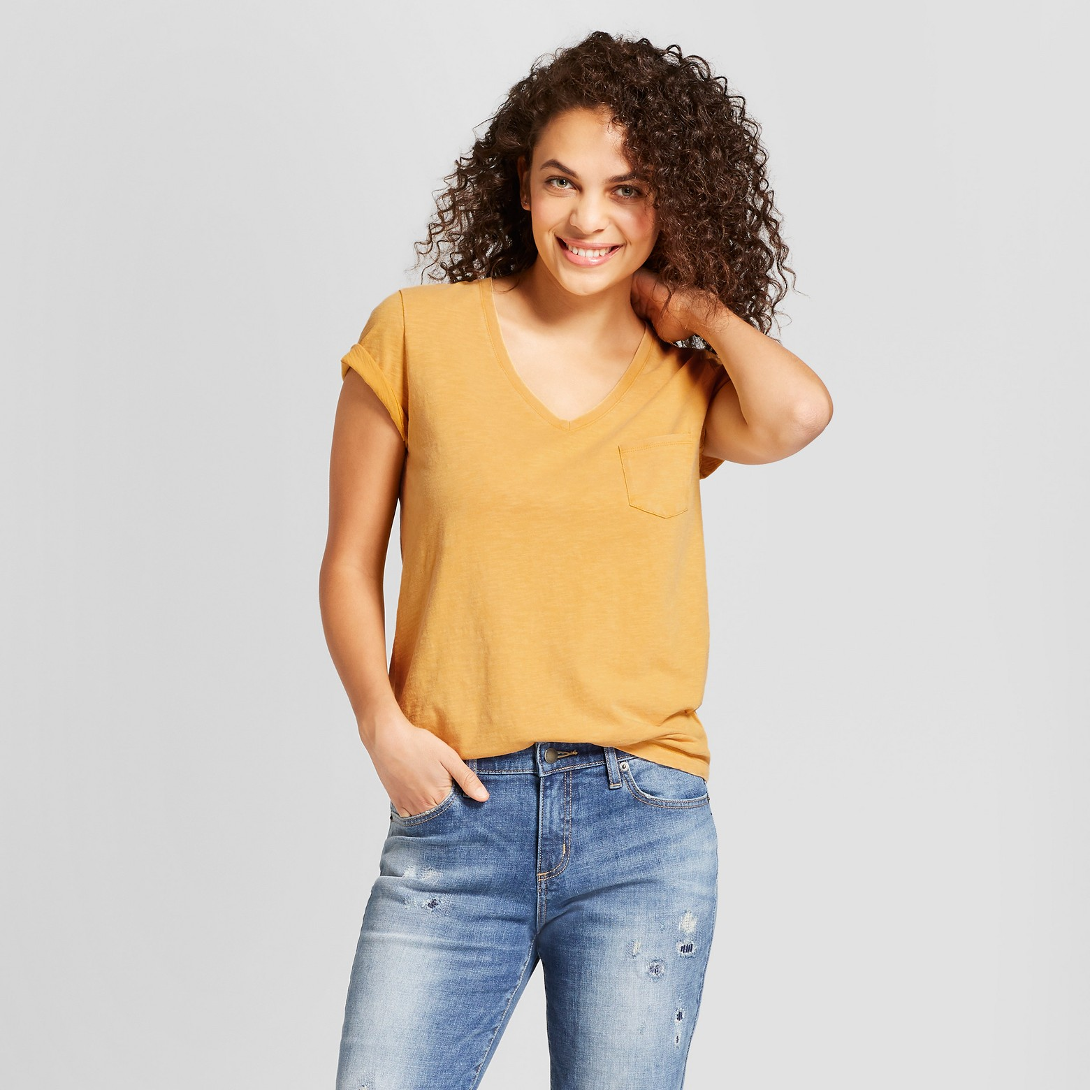 Woman wearing mustard colored V-neck with denim jeans.