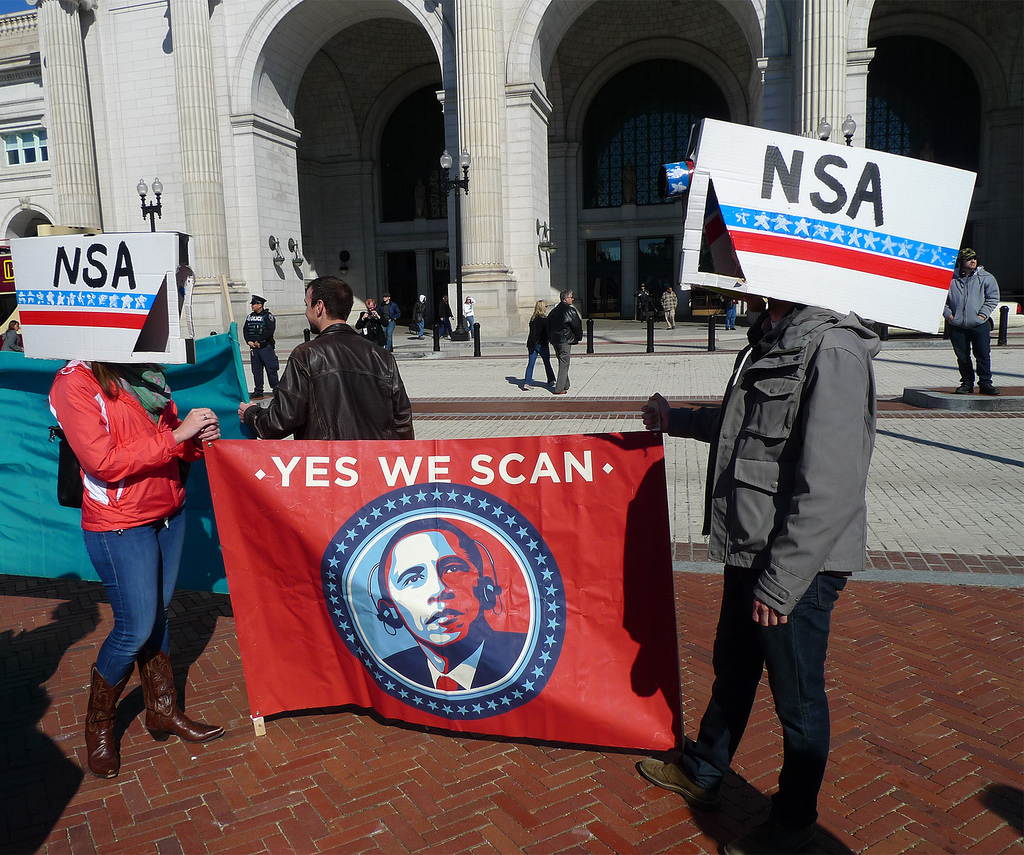 "protesters holding a sign that says ""yes we scan"" and has a picture of Obama"