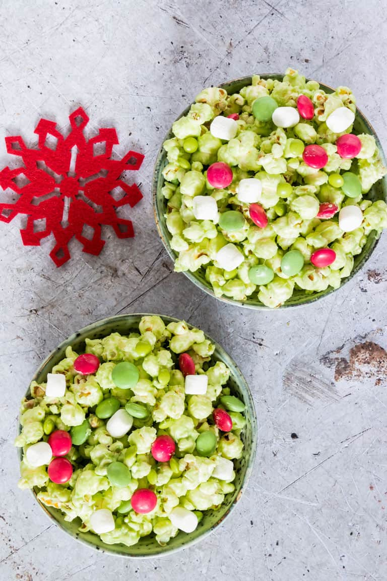 top down view of two ceramic bowls filled with Grinch Popcorn on a countertop and set next to a festive red snowflake coaster