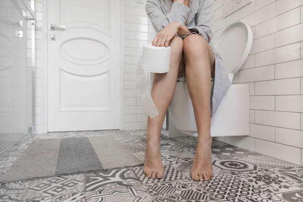 Woman sitting on the toilet holding toilet paper Woman sitting on the toilet holding toilet paper in her hands a lady peeing stock pictures, royalty-free photos & images