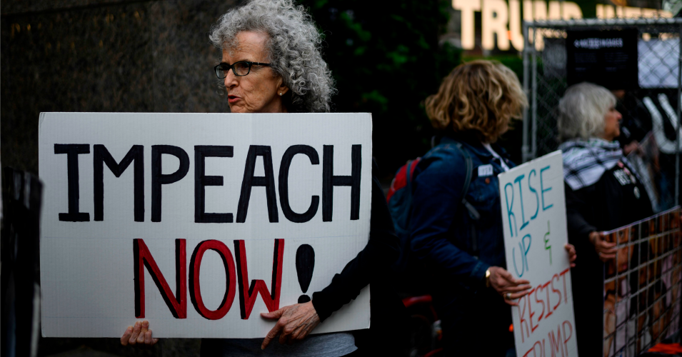 "A demonstrator with a sign reading ""impeach now"""