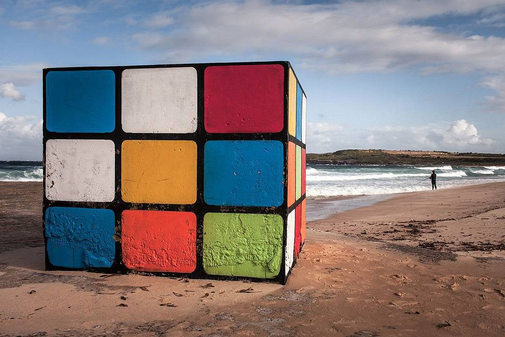 the big rubik's cube is a concrete blog painted to look like a rubik cube on a beach