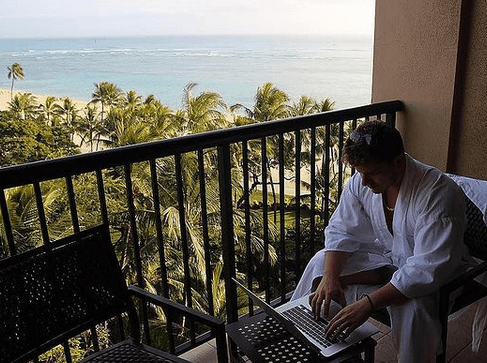 Justin Woll working on a laptop from a hotel balcony with an ocean view ecommerce university