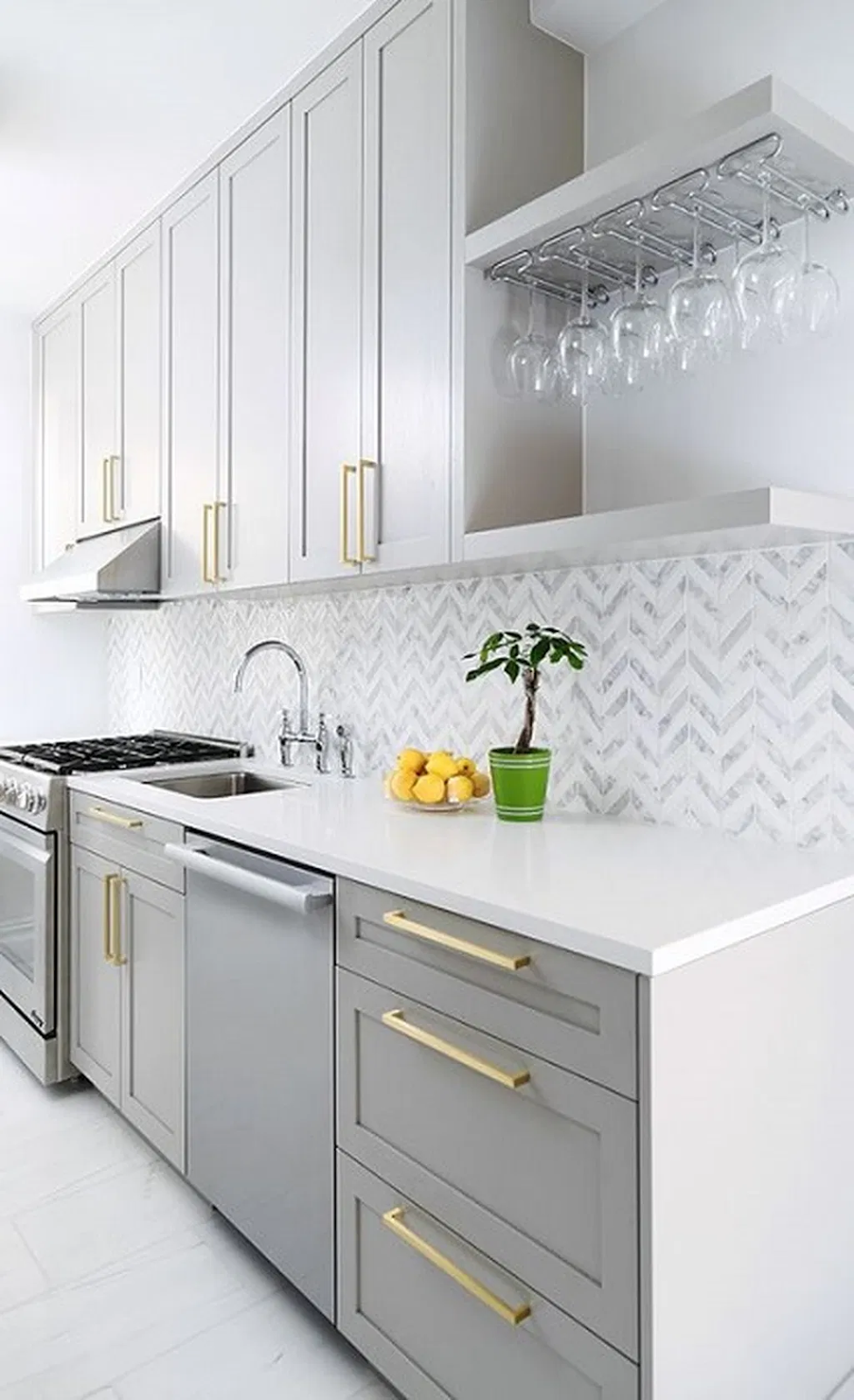 light grey and white kitchen with grey shaker cabinets, brass cabinet pulls and a geometric grey and white backsplash
