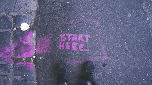 """start here"" written on the sidewalk in chalk"