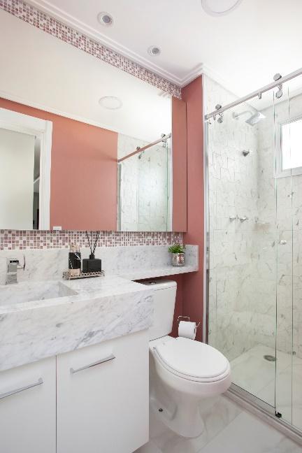 Banheiro com pastilhas em forma de faixa decorando somente em volta do espelho, pia de mármore, box de vidro e piso porcelanato.