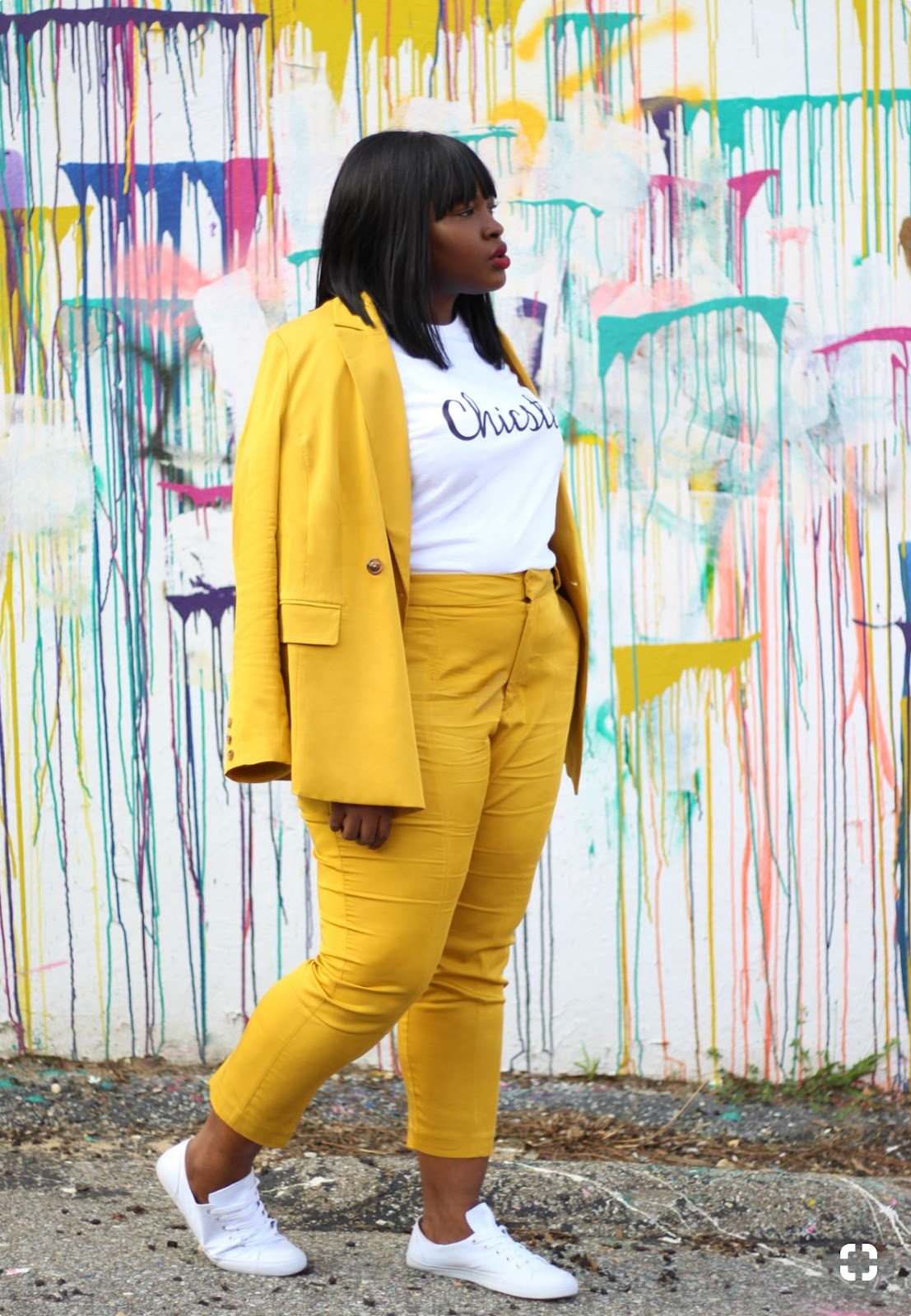 A woman is wearing a bright yellow blazer and cropped pants