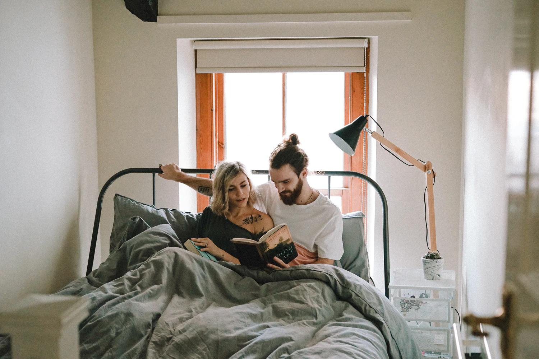 Пара читает книгу в постели