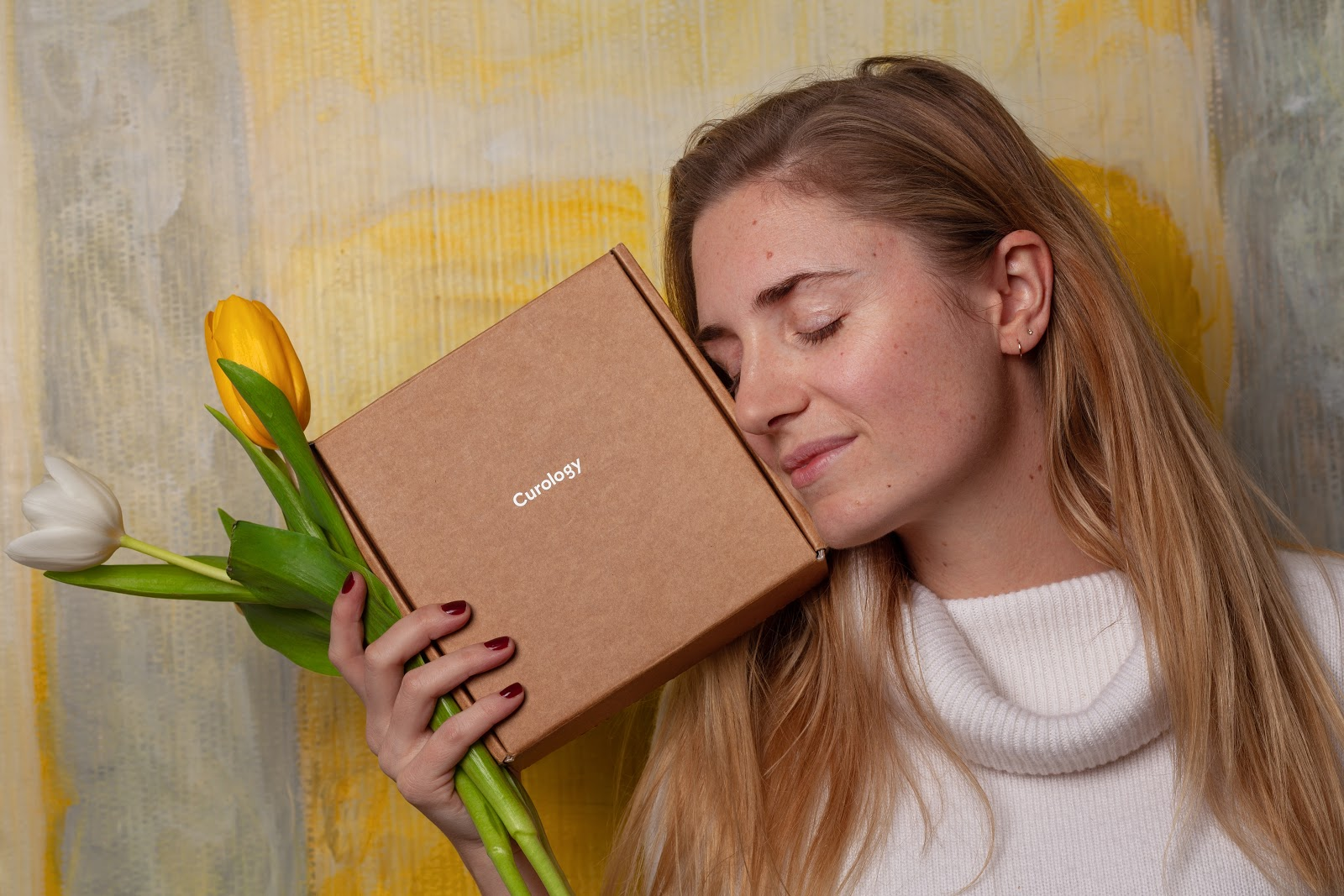 Whoman holding flowers and a custom shipping box next to her face