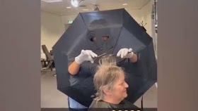 Coronavirus, the hairdresser cuts holes in an umbrella for her hands - in order to avoid contact with clients