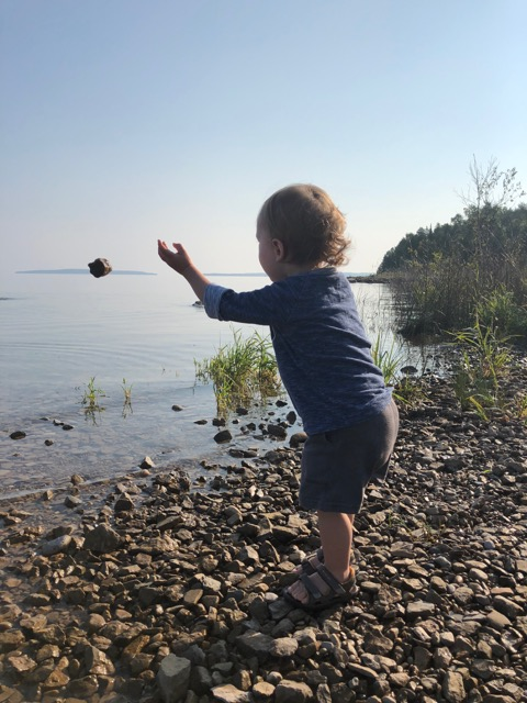 A toddler throwing rocks into the water.