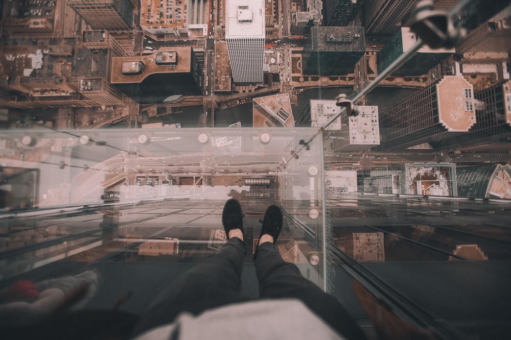 Persona mirando hacia las calles de abajo a través del piso de cristal en rascacielos
