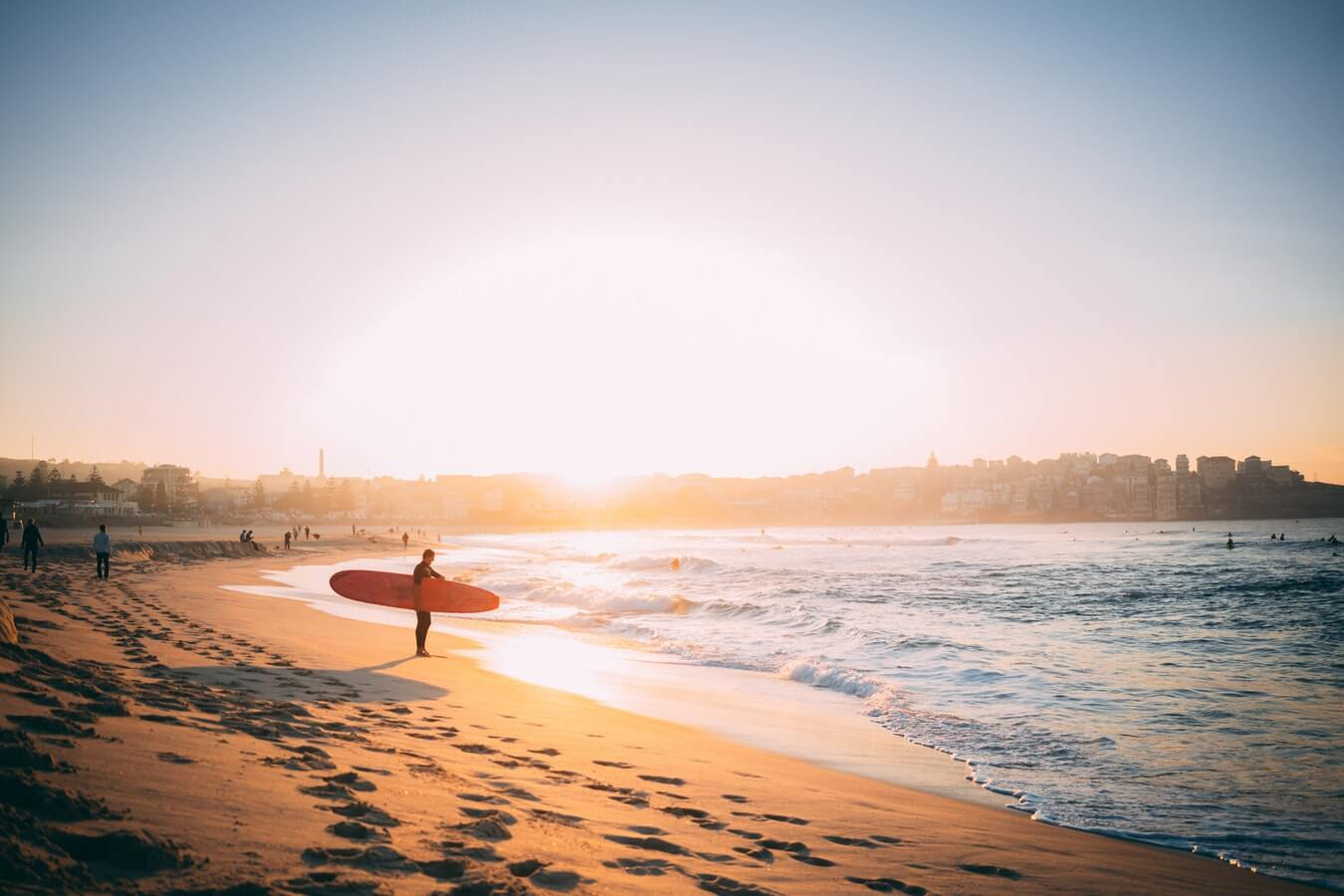 Surfer on beach with longboard. Vacation houses Australia