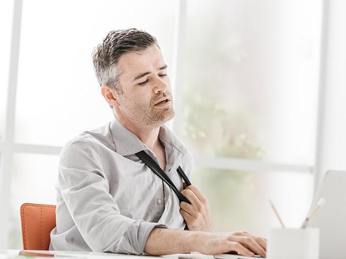 Mann sitzt am Schreibtisch und lockert sich seine Krawatte: Vermehrtes Schwitzen tritt bei Diabetes vor allem bei Unterzuckerung auf.