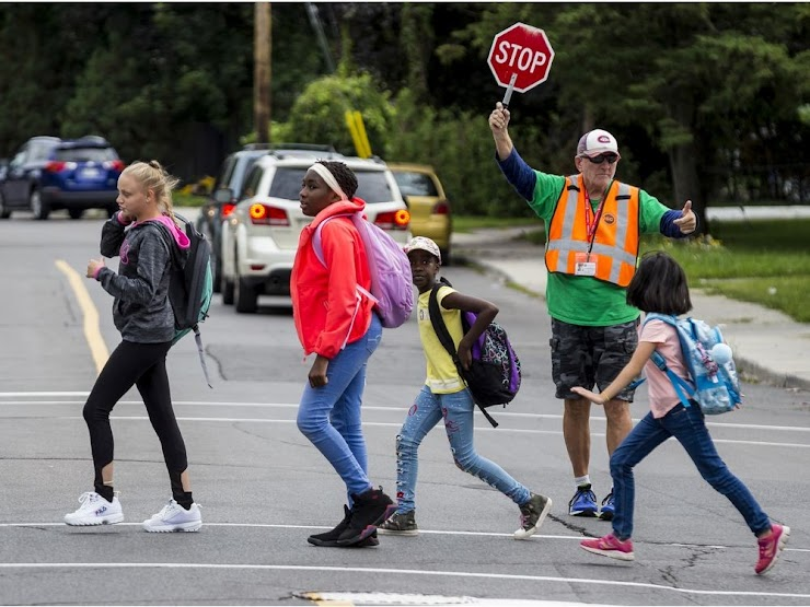Picture: A crossing guard assists school children to safely cross a road.