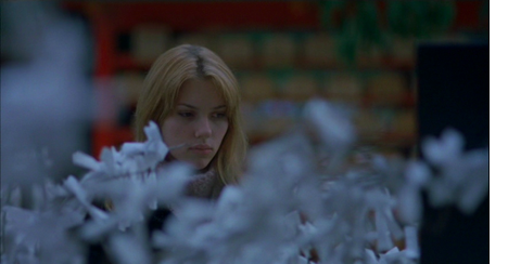 Scarlett Johansson as Charlotte in Lost in Translation (2003). Charlotte, a young white American woman, is standing in a store, her surroundings are blurred in a shallow focus - the only clear detail is her sombre expression.