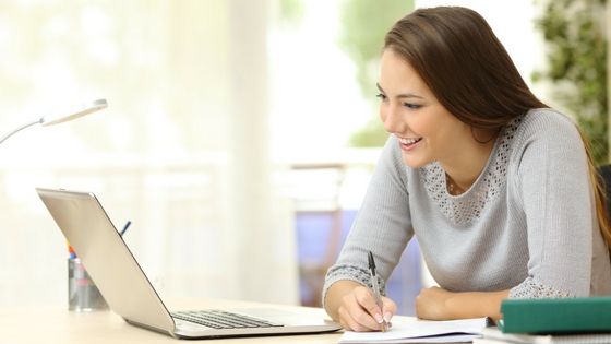 Woman looking at a laptop screen at floor plans