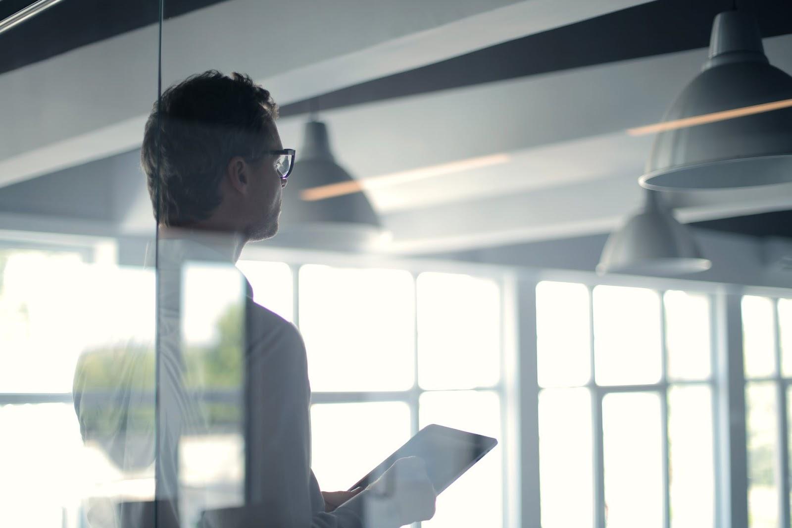 Uma pessoa de costas com um tablet em suas mãos.