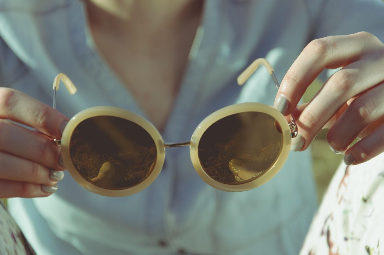 משקפי שמש אופנתיות מוחזקות בידי אישה