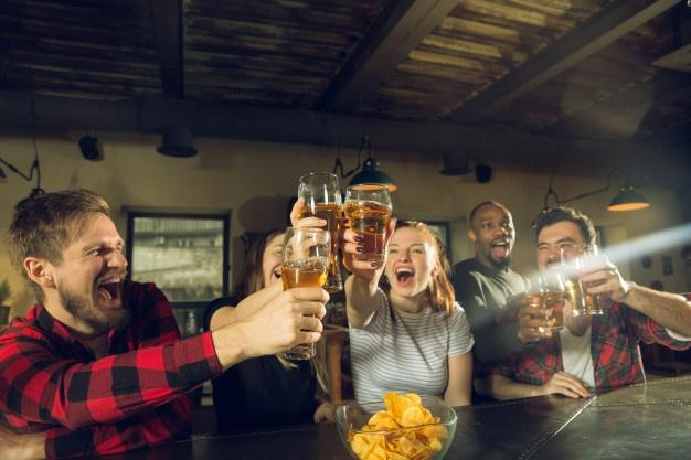 Sport fans cheering at bar, pub and drinking beer while championship, competition is going drink beer