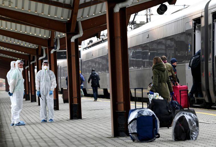 Сотрудники железной дороги в защитных костюмах и масках направляют пассажиров на спецпоезд сообщением «Перемышль — Киев» на железнодорожном вокзале в Перемышле, Польша, 20 марта 2020 года. Украина приостановила международное и внутреннее железнодорожное пассажирское сообщение на время усиленных мер безопасности из-за распространения коронавируса