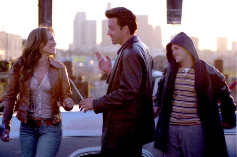 Still from Gigli (2003). Gigli and his friend stand beside a car on a sunny street, and he gestures towards Ricki, a girl walking away from him but who turns to smile at him.