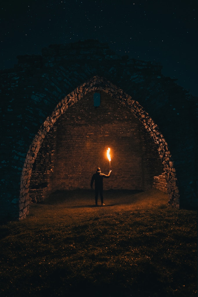 A man stands with a torch under a dark arch as an example of Snyder's All is Lost moment under story plot structure.