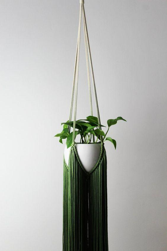Macramê em formato de suporte de vaso de planta.