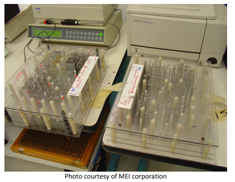 A white bed of Nails Bare PCB Test fixture with multiple probes connected, photo courtesy of MEI corporation.