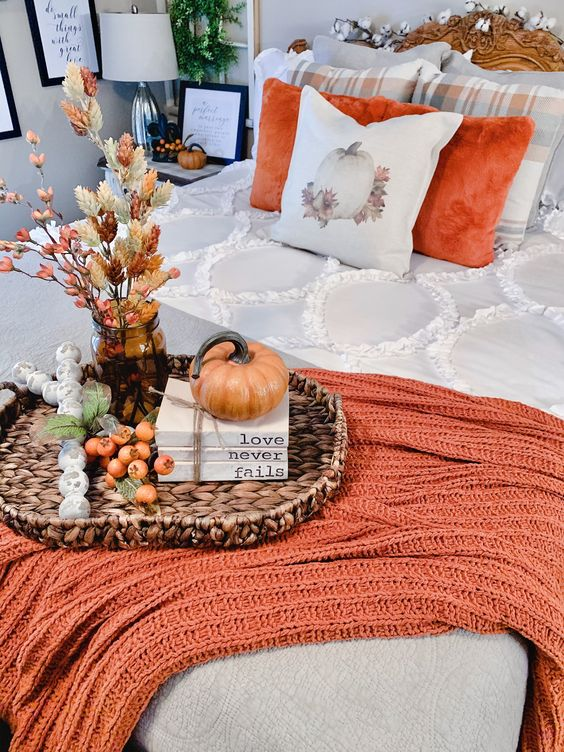 Image shows bed with orange throw pillows and one with a pumpkin on it. as well as a orange throw blanket and pumpkins and fall leaves in a vase.