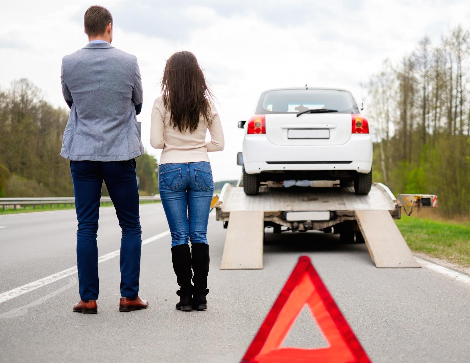 Um casal olhando seu carro sendo guinchado.
