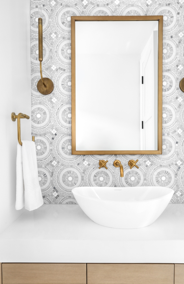small modern bathroom with white ceramic vessel sink, brass hardware and creative patterned wallpaper
