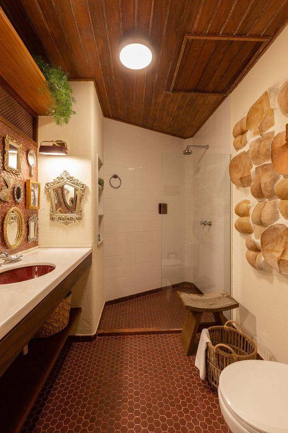 Banheiro com piso hexagonal de madeira em formato pequeno, revestimento de madeira no teto, azulejos brancos, pedras decorativas numa parede, bancada branca da pia e parede da pia com diversos espelhos e bancos e cestos de madeira.