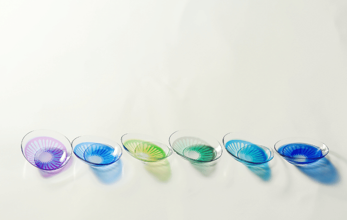 An image of different colours of contact lenses, shown from left to right: purple, blue, lime green, green, aqua, deep blue