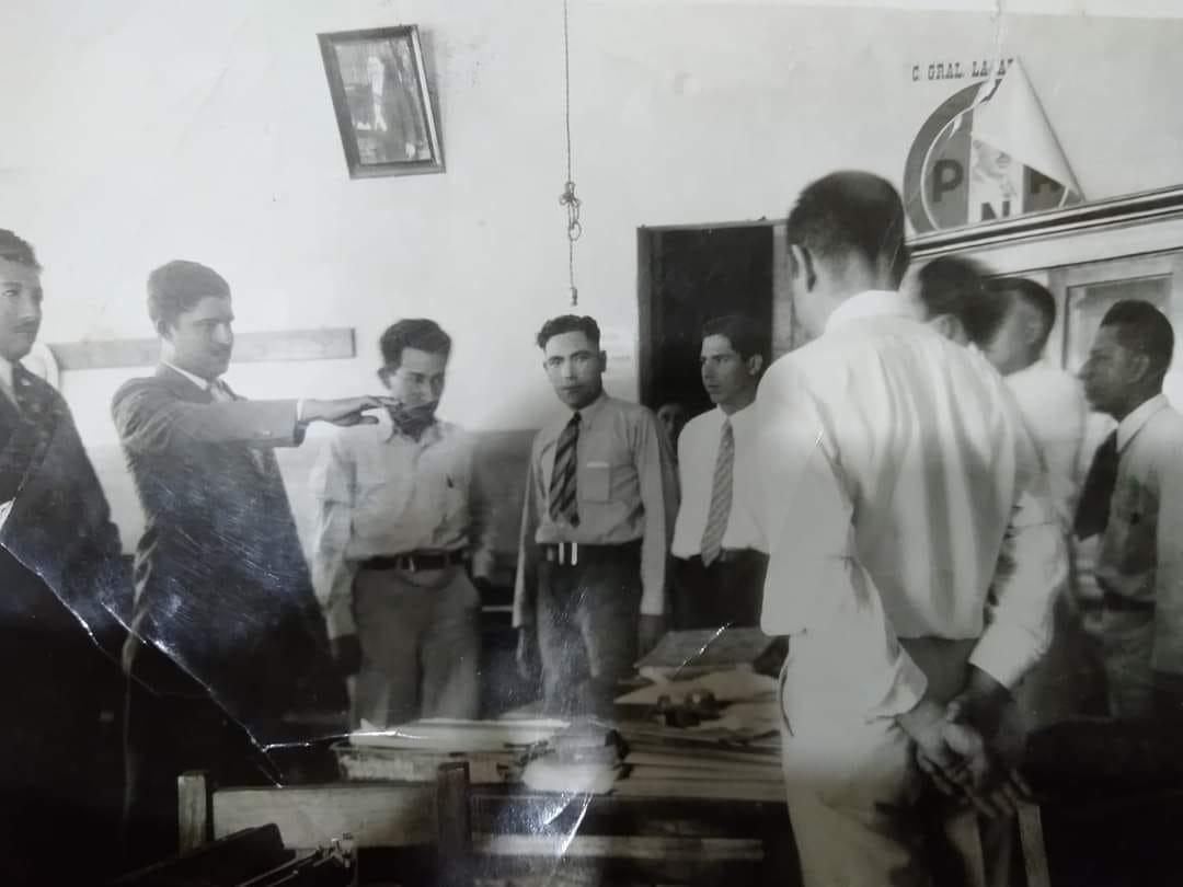 Foto en blanco y negro de un grupo de personas alrededor de una mesa  Descripción generada automáticamente