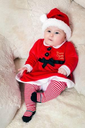 Cute little christmas baby wearing santa claus suit, with a funny look. Stock Photo - 83434691