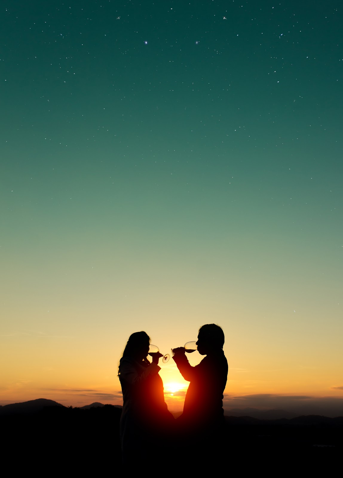 two people drinking wine in the sunset