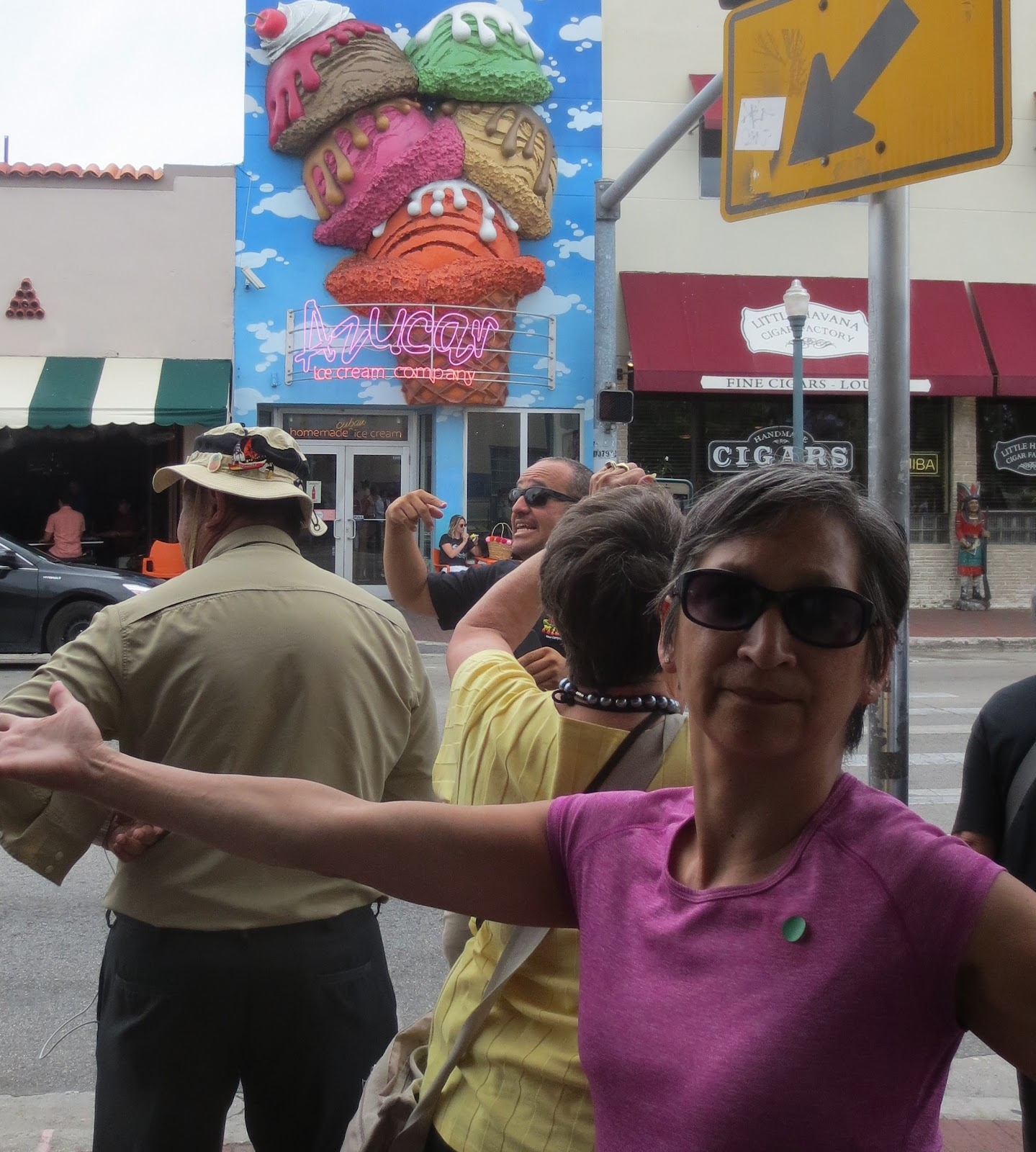TOCTooler Pat Lim.  Street scene, before crossing street: arms spread, sunglasses on, smiling as she points to an exceptionally large ice cream shop sign across the street