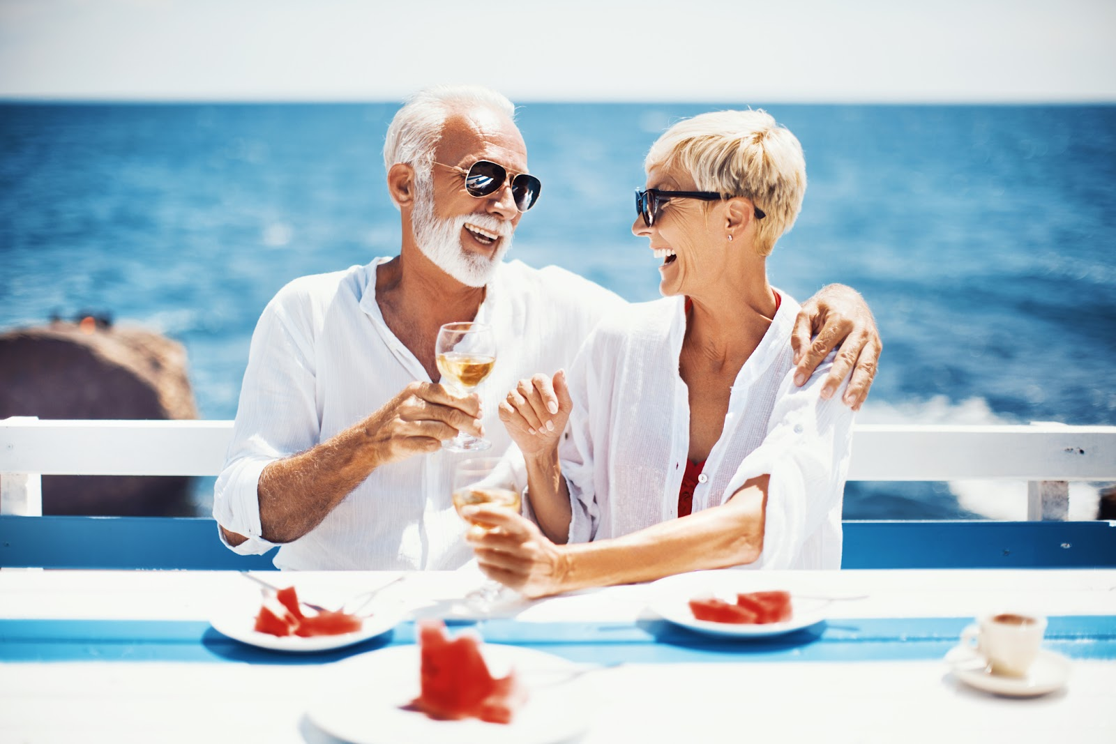 A mature man and woman raise a toast while drinking wine near the water