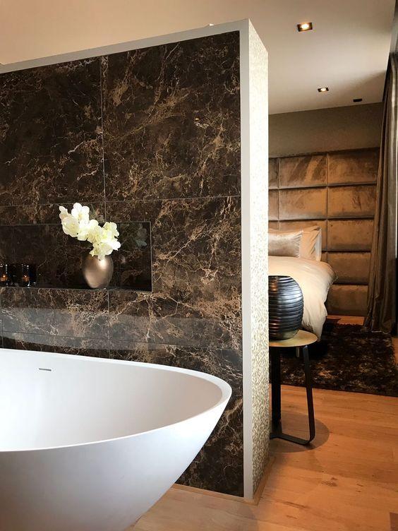 Banheiro com uma parede revestida de porcelanato marmorizado escuro, piso de madeira e banheira branca.